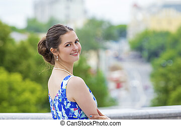 Beautiful young woman on the urban background.