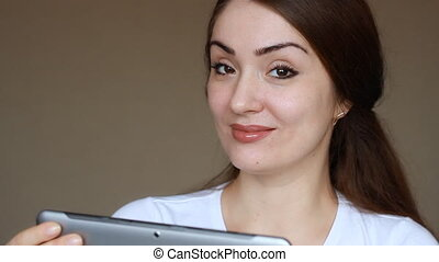 Beautiful young woman online banking using tablet computer...