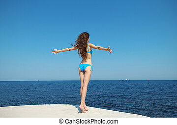 Beautiful young woman opened her hands with delight at the blue sky