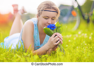 Beautiful Young Woman Outdoors. Calm Relaxing Girl on Green Grass Smelling Flowers Bouquet. Horizontal Image