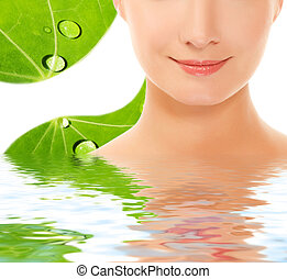 Beautiful young woman over green leaf background reflected...