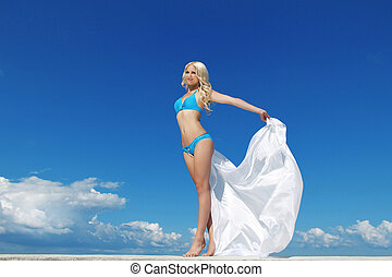 Beautiful young woman over the blue sky with white drapery