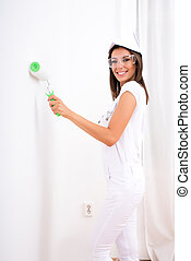 Beautiful young woman painting a Apartment