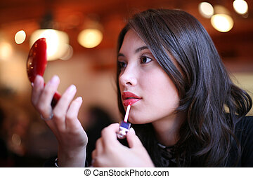 Beautiful young woman painting lips
