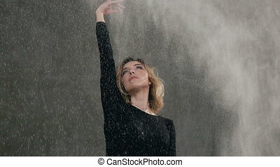 Beautiful young woman perform modern dance in studio against gray background with of splashes white powder or dust. Portrait of cute girl who dance in indoor while looking at the camera