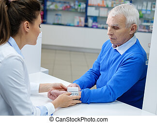 Beautiful young woman pharmacist measuring blood pressure to senior man customer in pharmacy.