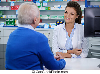 Beautiful young woman pharmacist talking with senior man customer in pharmacy.