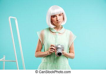 Beautiful young woman photographer holding photo camera