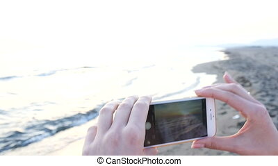 beautiful young woman photographing sunset on the beach using a smartphone