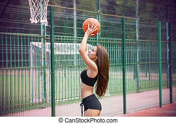 Beautiful young woman playing basketball outdoors