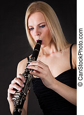 Beautiful young woman playing clarinet