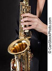 Beautiful young woman playing saxophone
