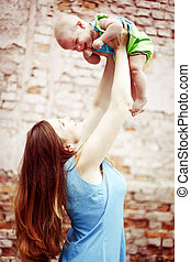 Beautiful young woman playing with baby