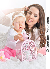 Beautiful young woman playing with little daughter