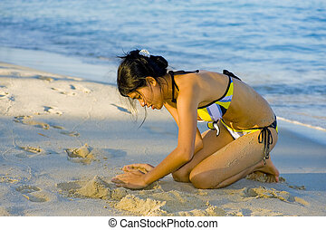 beautiful young woman playing with the sand