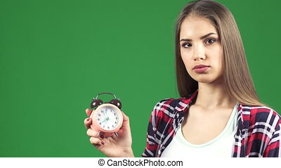 Beautiful young woman pointing at the alarm clock looking serious