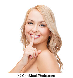 beautiful young woman pointing finger to lips