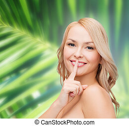 beautiful young woman pointing finger to lips - health and...