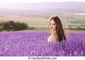Beautiful young woman portrait in lavender field. Attractive brunette girl with long healthy hair style enjoying countryside life.