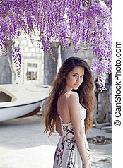Beautiful young woman portrait over wisteria blossom. Attractive brunette girl with long healthy hair in white dress smiling at camera.