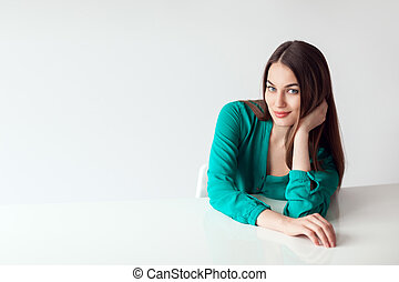 Beautiful young woman portrait sitting at the table on white background
