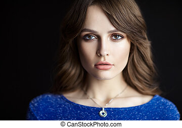 Beautiful young woman portrait with long hair on black background