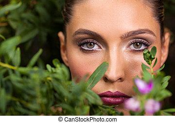 young woman posing among green leaves