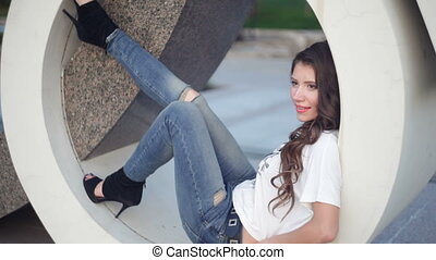 beautiful young woman posing in a circle sculpture.