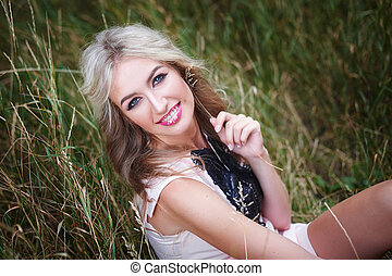 beautiful young woman posing in a summer park