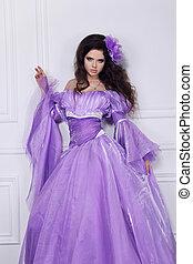 Beautiful young woman posing in elegant dress