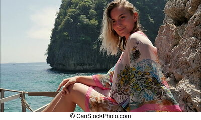 Beautiful young woman posing in photo session with the sea...
