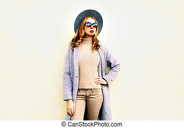 beautiful young woman posing in pink coat, round hat on wall background