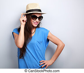 Beautiful young woman posing in straw hat and fashion sun glasses on blue background with empty copy space