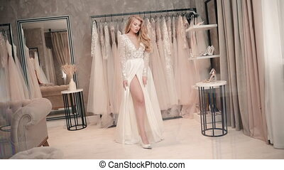 Beautiful young woman posing in white wedding dress while standing at clothing store. Attractive American female dressed in stylish gown touches her bare leg and moves body sensually in bright room. Millennial girl model poses and present in fashion shoot for magazine. Concept: bridal, luxury, ...