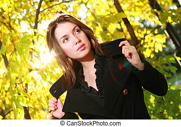 Beautiful young woman posing in yellow autumn forest.