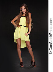 Beautiful young woman posing in yellow dress isolated on black background