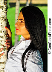 Beautiful young woman posing near the green tree on nature
