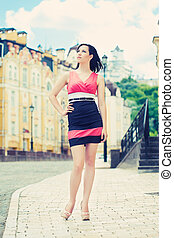 beautiful young woman posing on a city street