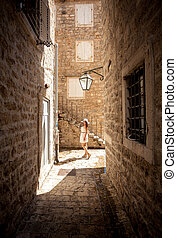 young woman posing on old narrow street at sunny day