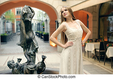 beautiful young woman posing on the street showing dresses...