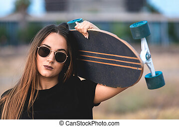 Beautiful young woman posing with a skateboard on sunset