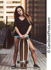 Beautiful young woman posing with skateboard
