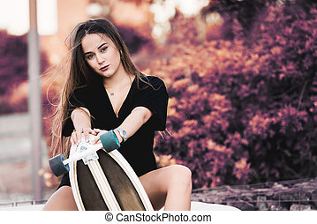 Beautiful young woman posing with skateboard