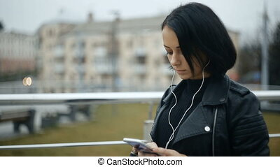 Beautiful young woman prints text in smartphone, listening to music on headphones