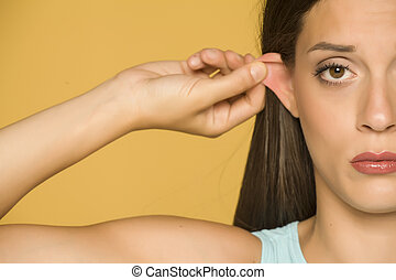 Beautiful young woman pulling her ear with her fingers on yellow background