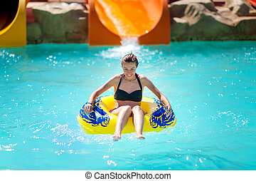 beautiful young woman pulls off the slides in water park