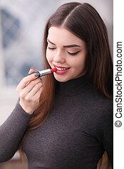Beautiful young woman putting lipstick on lips