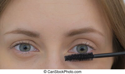 Beautiful young woman putting mascara - Close up shot....