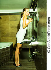 Beautiful young woman putting on makeup in the bathroom