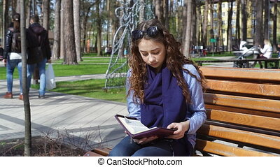 beautiful young woman reading a book on a park bench